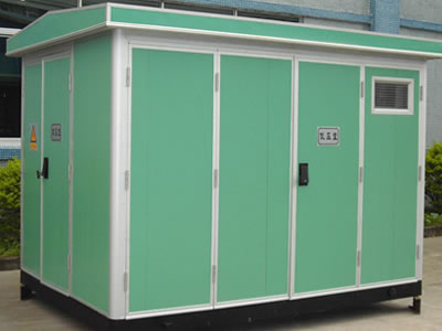 A green prefabricated substation is on the ground.
